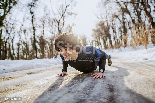 Dedicated fit cheerful caucasian man in sportswear and with curly hair doing push ups on track. Wintertime. Outdoor fitness concept.