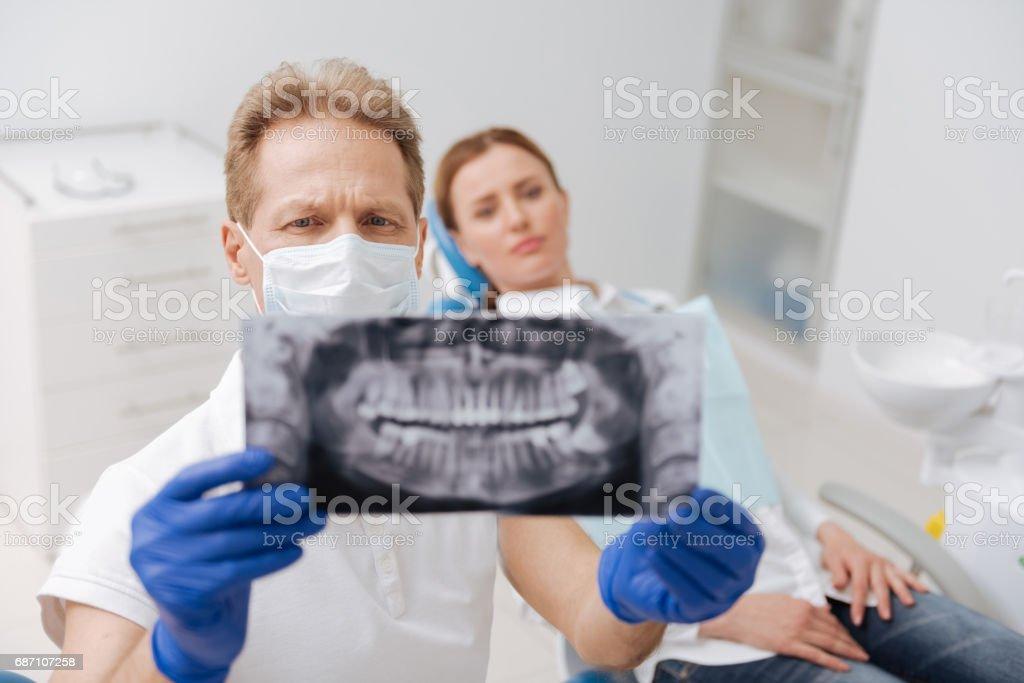 Dedicated learned dentist studying patient jaw scan Lizenzfreies stock-foto