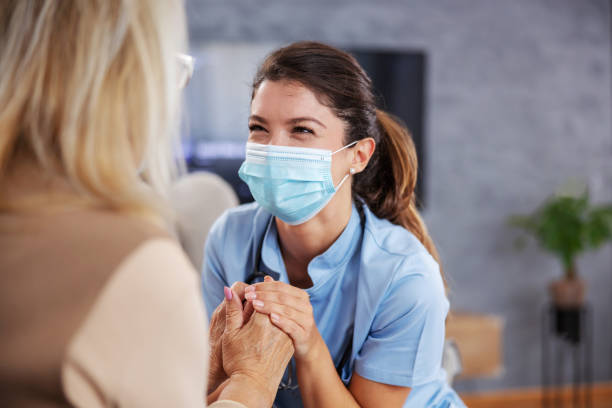 Dedicated nurse with face mask sitting at home with senior woman, holding her hands and comforting her. stock photo