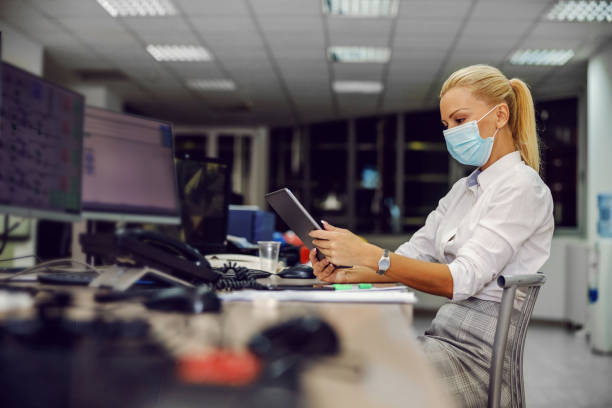 Dedicated serious female CEO in suit with face mask sitting in control room in heating plant, controlling employees over tablet during corona outbreak. stock photo