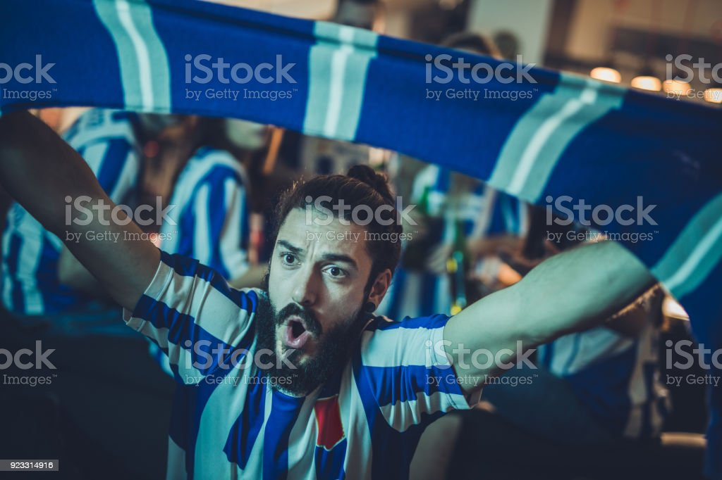 Young man cheering for his favorite soccer team while watching a...