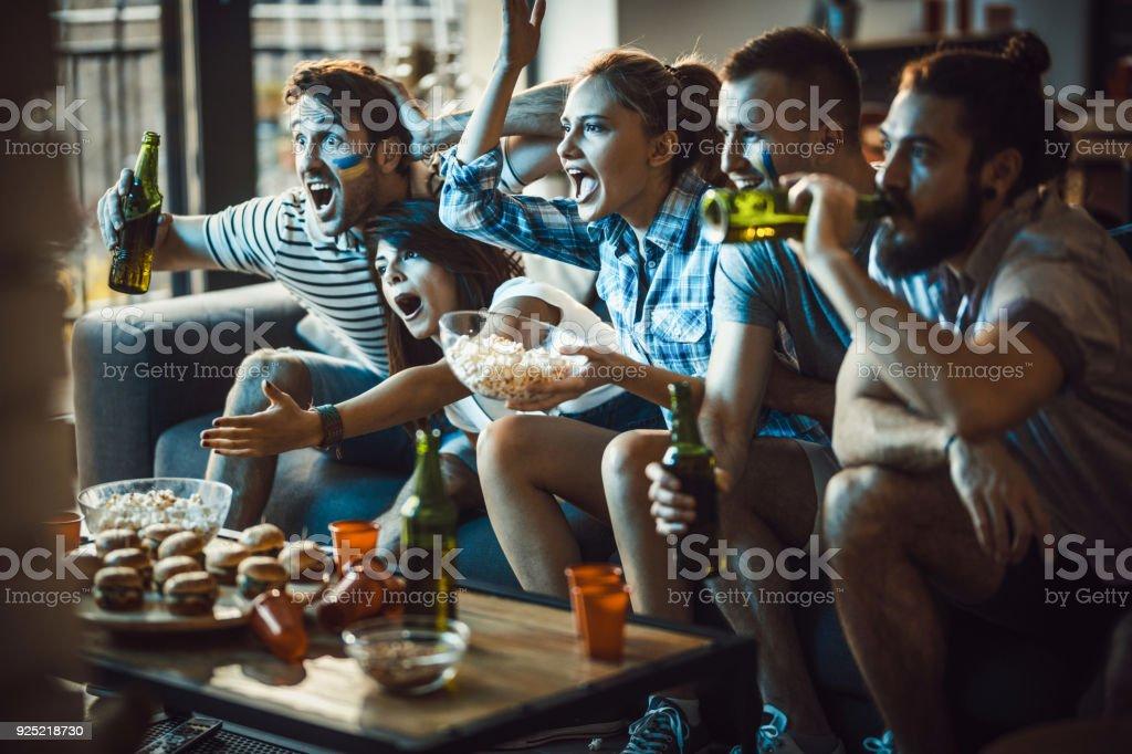 Dedicado a fãs de esportes, assistindo um jogo na TV na sala de estar. - foto de acervo