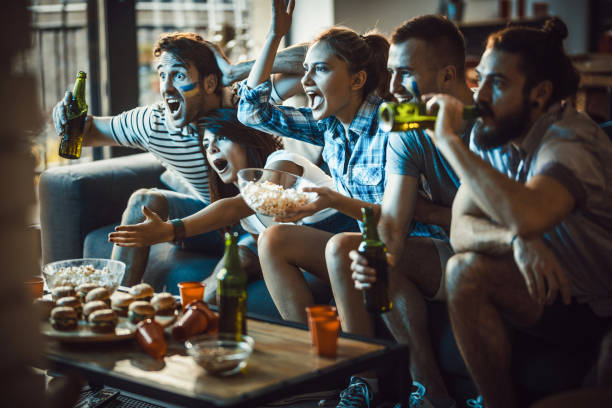Dedicated sports fans watching a game on TV in the living room. stock photo