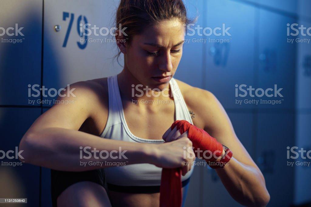 Sportswoman dedicado que envolve a mão com atadura antes do treinamento dos esportes. - foto de acervo