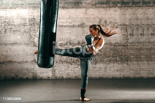 istock Dedicated strong brunette with ponytail, in sportswear, bare foot and with boxing gloves kicking sack in gym. 1126503889