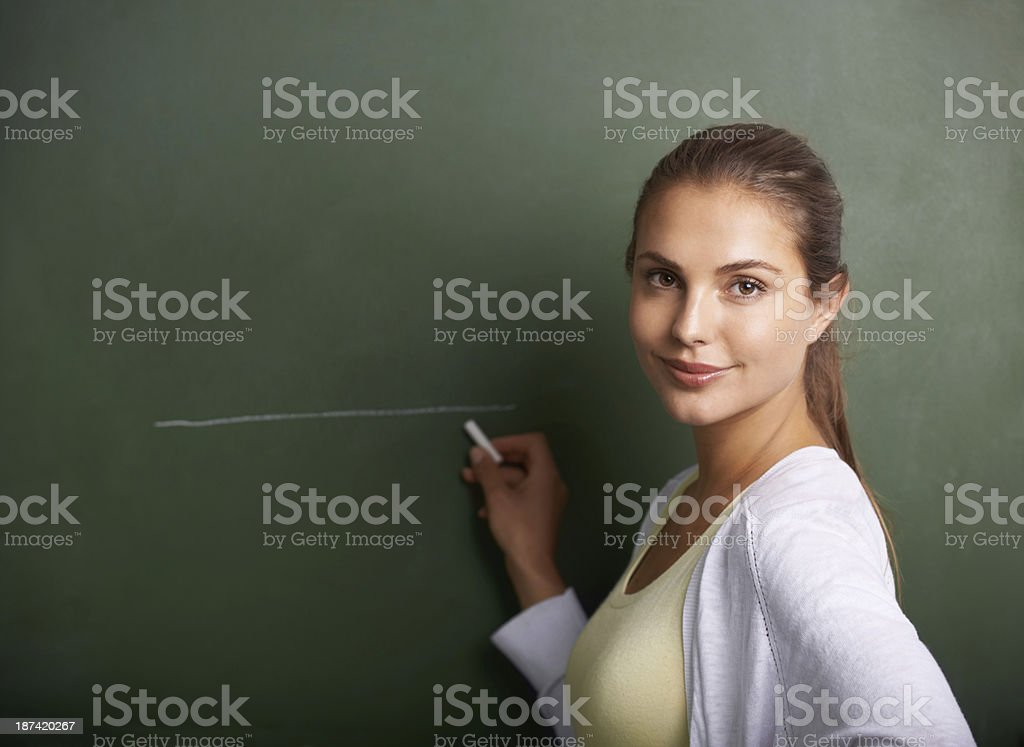 A beautiful young teacher writing on a blackboard while smiling at...
