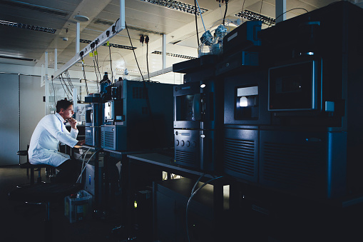 Lone male scientist looking at data on a computer screen surrounded by medical machinery.