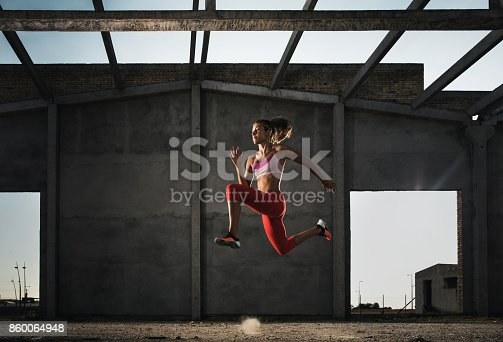istock Dedicated woman jumping in a run on a sports training. 860064948