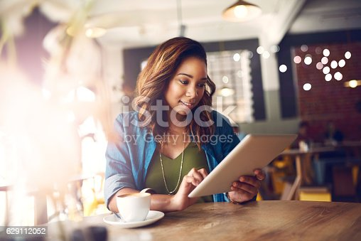 Cropped shot of an attractive young woman using a digital tablet in a cafe