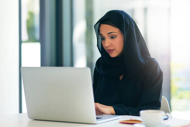 dedication and technology. essential for getting her tasks done - saudi woman stock photos and pictures