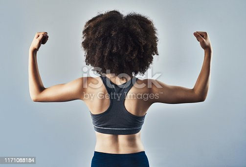 Studio shot of a sporty young woman flexing her arms against a grey background