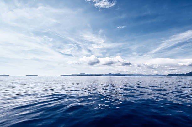 Deep Blue Ocean Dramatic cloudscape over the deep dark blue ocean. Beautiful seascape with reflection on the water on the sunrise.See more images like this in: atmospheric mood stock pictures, royalty-free photos & images