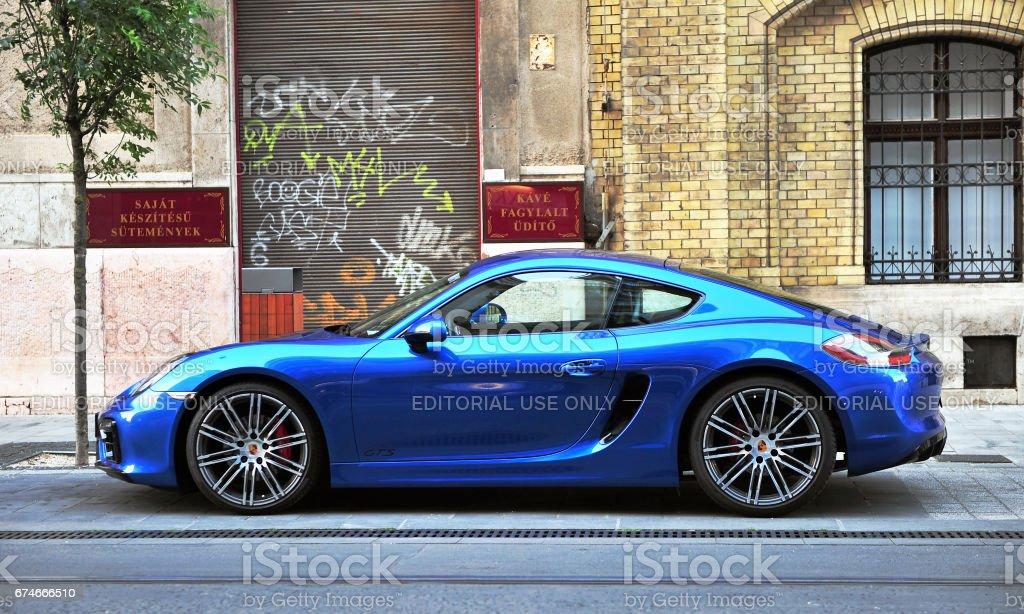 Deep blue Porsche Budapest, Hungary - May 20, 2016: Deep blue Porsche sport car in the street of Budapest on May 20, 2016. Porsche is a global automobile manufacturer headquartered in Stuttgart, Germany. Blue Stock Photo