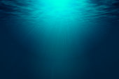 Deep blue sea with rays of sunlight, ocean surface seen from underwater. Background texture with copy space for text or product display.
