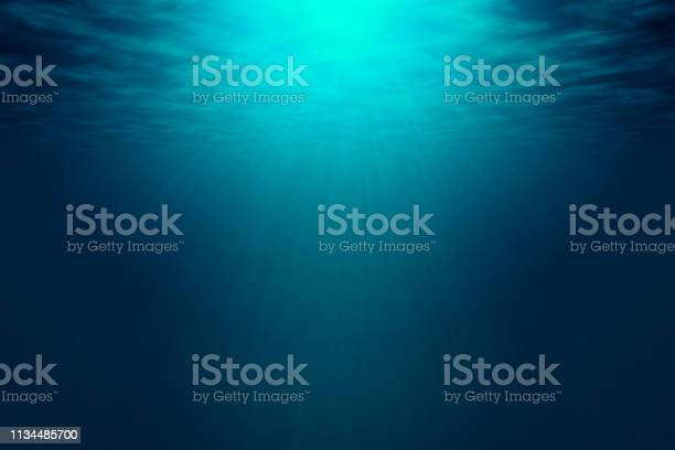 Photo of Deep blue sea with rays of sunlight, ocean surface seen from underwater.