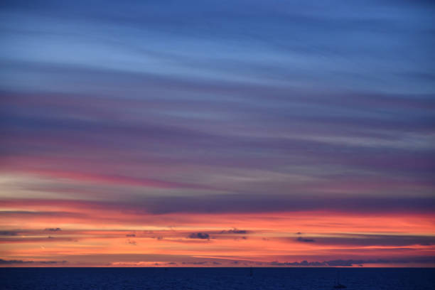 deep blue sea with vibrant sunset and sailboat - steven harrie stock pictures, royalty-free photos & images