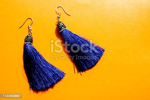 Closeup top view of two royal blue tassel earrings. The set is isolated on orange platform.
