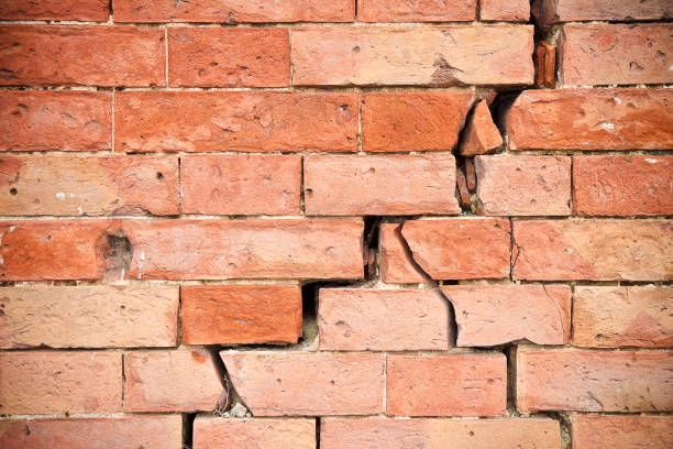 deep crack in old brick wall - concept image - stability stock photos and pictures