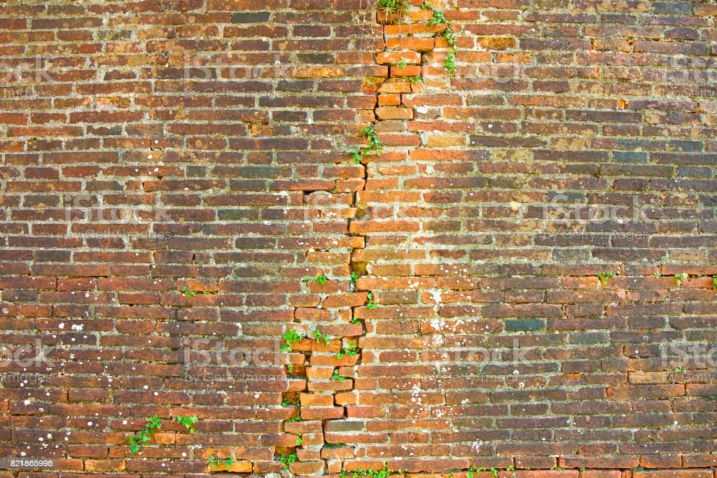Deep crack in old brick wall - concept image stock photo