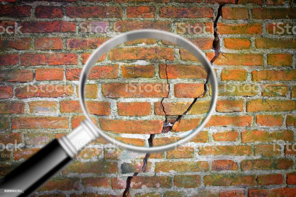 Deep crack in old brick wall with magnifying glass - concept image stock photo