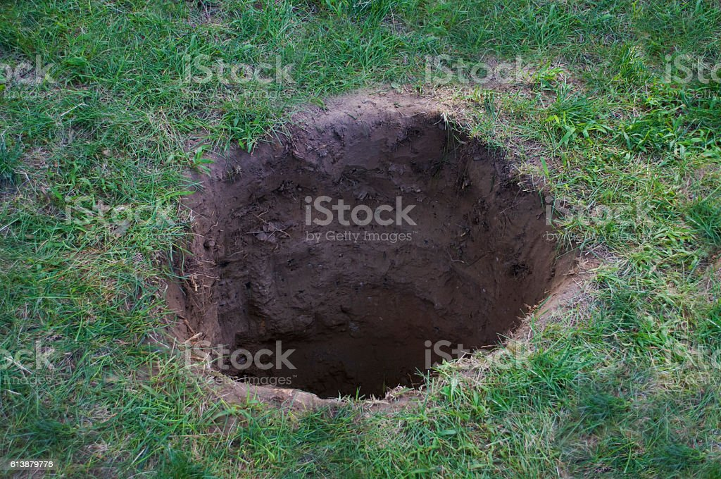 Deep dirt hole in ground or lawn stock photo