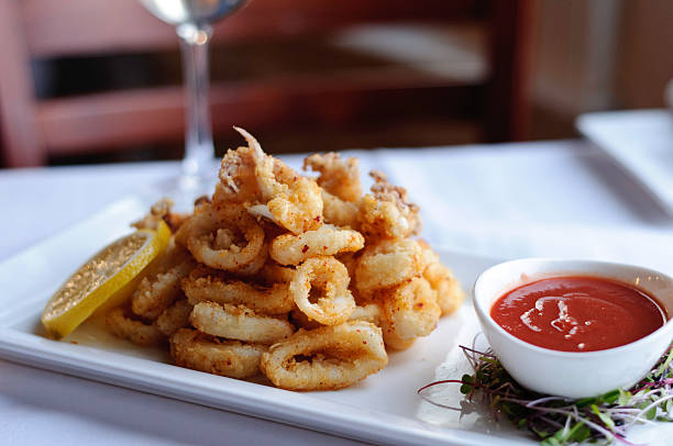 Deep fried calamari with lemon slices and red dipping sauce stock photo