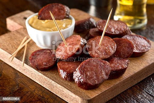 Delicious pub style deep fried pepperoni on a wood serving board.