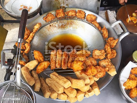 Deep fried tofu, taro, radish and corn street vendor. The frying oil is placed in the middle, heated at a high temperature after placed on the drying rack for the excess oil to drip off.