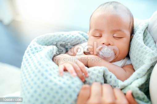 High angle shot of an adorable baby boy sleeping in his mother's arms