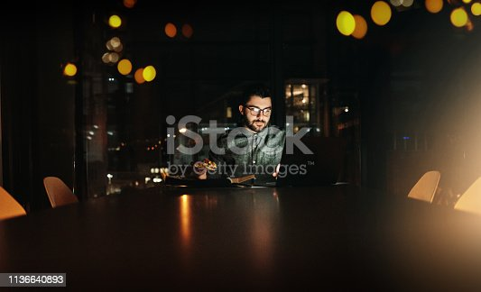 Shot of a young businessman using a laptop during a late night at work