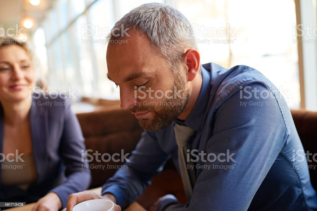 Deep in thought Bearded businessman looking in cup 2015 Stock Photo