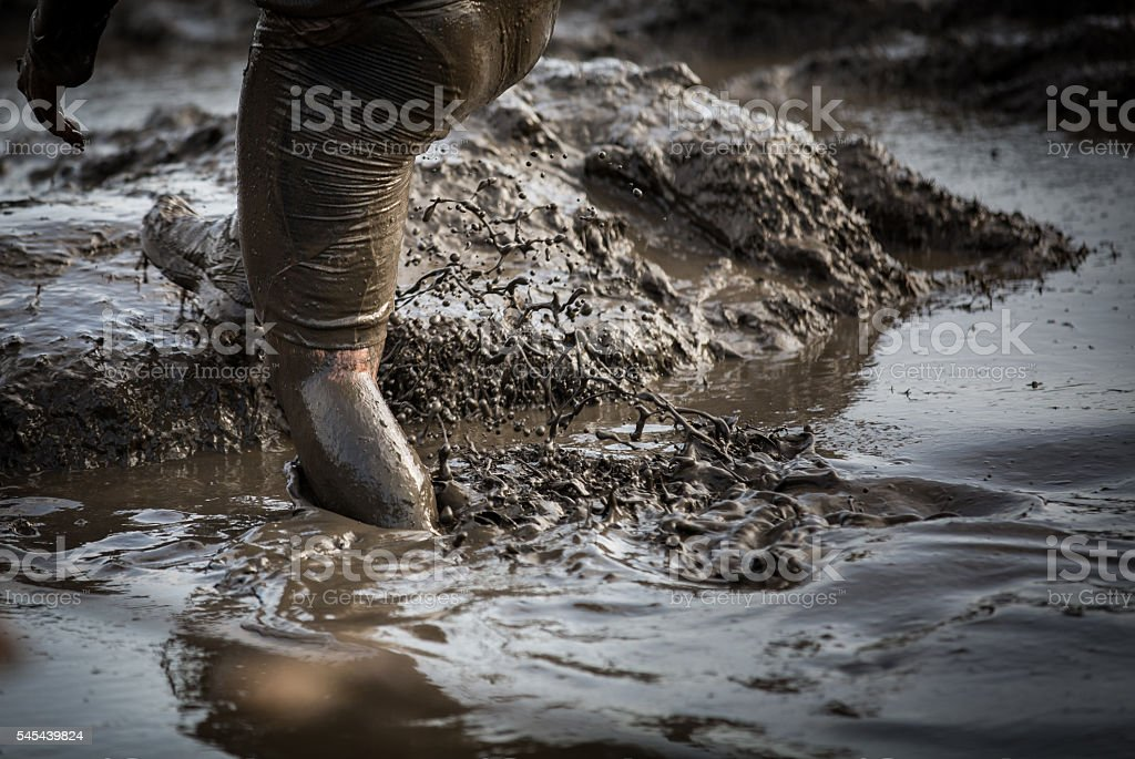 Deep muddy water with feet splashing and climbing stock photo