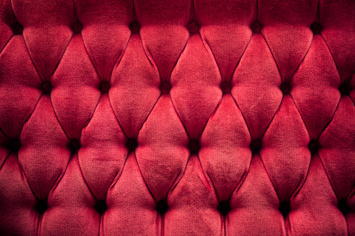 The back of a vintage red couch with diamond shaped quilted back.  Horizontal with copy space.
