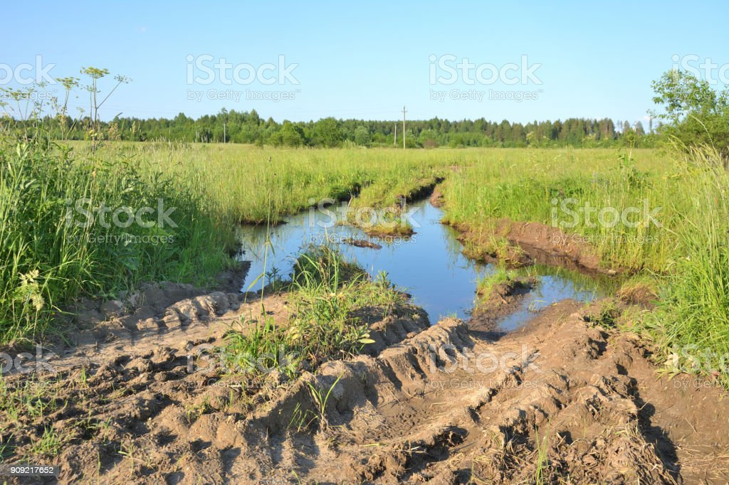 Deep ruts with water from a tractor on the edge of rural fields stock photo