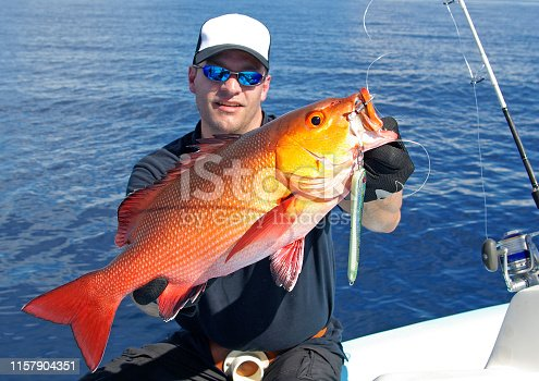 Catch of fish, big game fishing, Lucky  fisherman holding a red snapper fish