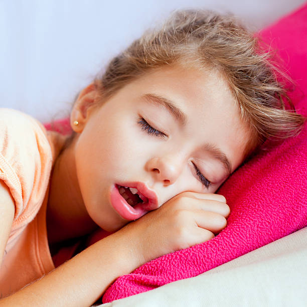 Deep sleeping children girl closeup portrait Deep sleeping children girl closeup portrait on pink pillow mouth open stock pictures, royalty-free photos & images
