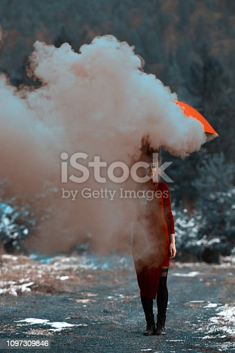 woman in the forest with umbrella, surrounded by deep gray smoke.