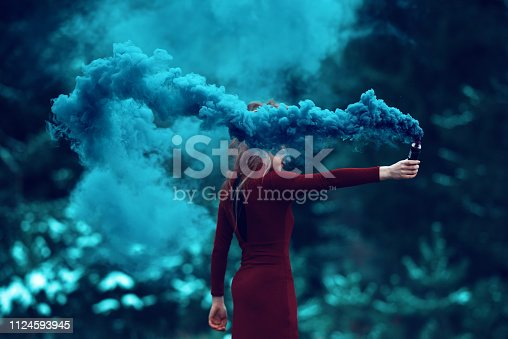 side view of woman in the forest holding flaming torch.