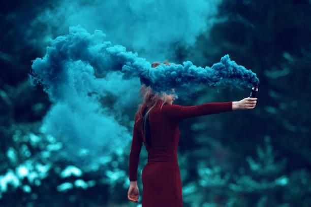 deep smoke from flaming torch side view of woman in the forest holding flaming torch. magician stock pictures, royalty-free photos & images