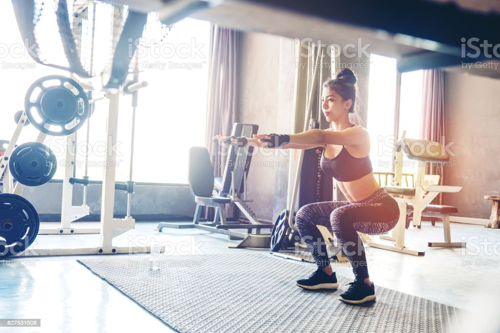 Deep squat of young beautiful woman in sportswear doing squat while standing in front of  glass at gym stock photo