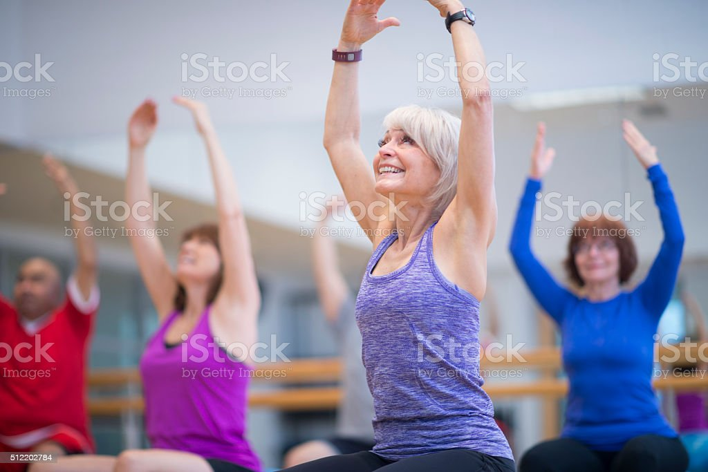 Deeply Stretching in a Fitness Class stock photo