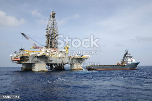 "Gulf of Mexico, USA - July 31, 2009: TransOcean's oil rig ""Deepwater Horizon"". The supply vessel ""Damon B Bankston"" operated by Tidewater is next to it. The rig made a record oil discovery for BP at the Tiber Prospect, GOM in 2009. The rig suffered a blow out while drilling at the Macondo Prospect in April 2010, then caught fire and sank  killing 11 and creating the worst oil spill ever in the Gulf of Mexico."