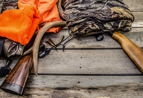 istock Deer Hunting Gear Background With Rifles, Rattling Antlers, Deer Call And Camouflage 871536754