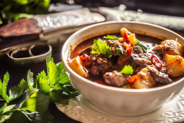 Deer stew in a bowl hunting weapon as a decoration. stock photo