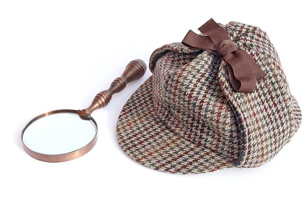 Deerstalker Cap and Vintage Magnifying Glass Deerstalker or Sherlock Holmes cap and vintage magnifying glass Isolated on white deerstalker hat stock pictures, royalty-free photos & images