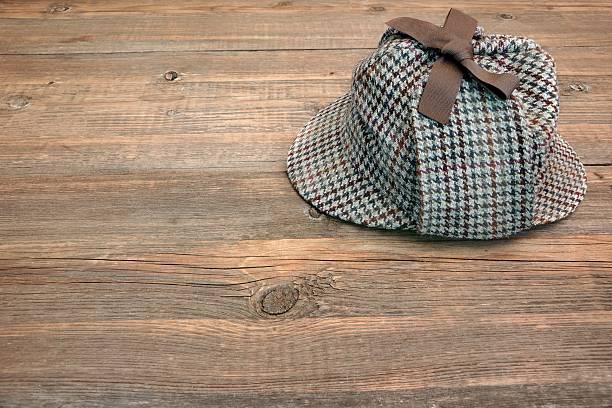 Deerstalker Detective hat On Wooden Table Isolated Deerstalker or Sherlock Hat on Wooden Table.  Background for text or image. deerstalker hat stock pictures, royalty-free photos & images