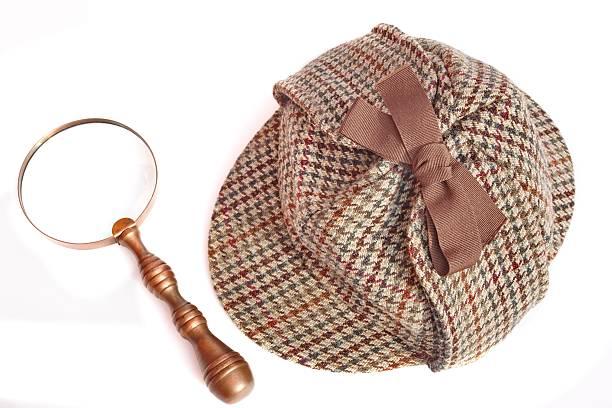 Deerstalker Hat And Magnifying Glass On Wooden Table Deerstalker or Sherlock Holmes cap and vintage magnifying glass Isolated on white deerstalker hat stock pictures, royalty-free photos & images