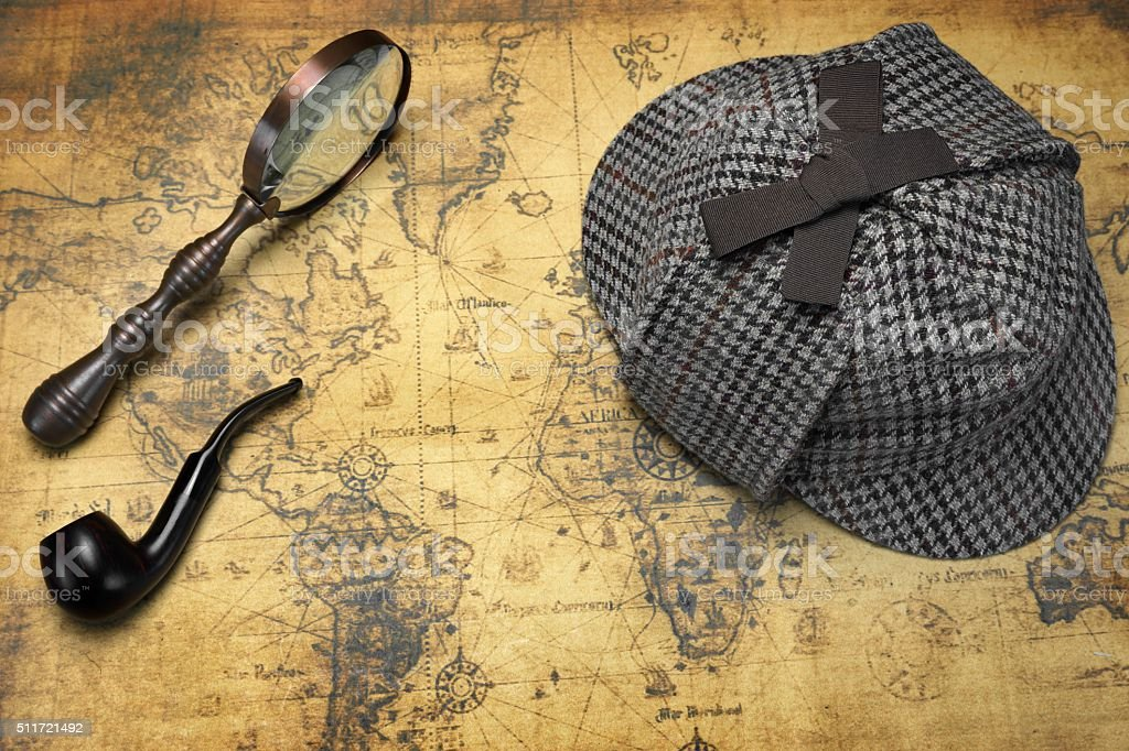 Deerstalker Hat, Magnifier And Smoking Pipe On Map Deerstalker Sherlock Holmes Hat, Vintage Magnifier And Smoking Pipe On The Old World Map Background. Overhead View.  Investigation Concept. Above Stock Photo