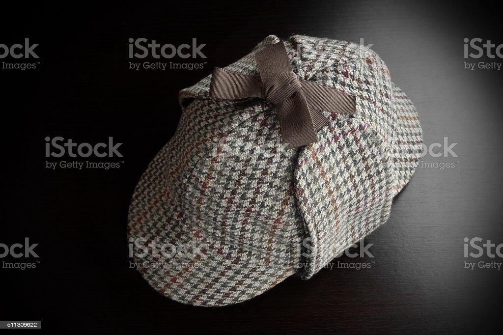 Deerstalker Hat On The Black Wooden Table stock photo