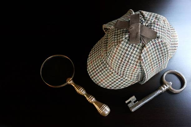 deerstalker, magnifier and smoking pipe on black table - sherlock holmes stock photos and pictures